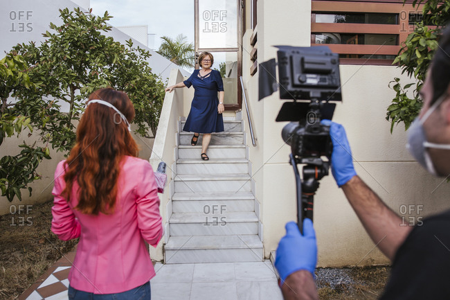 Senior woman moving down on steps while looking at reporter and camera operator