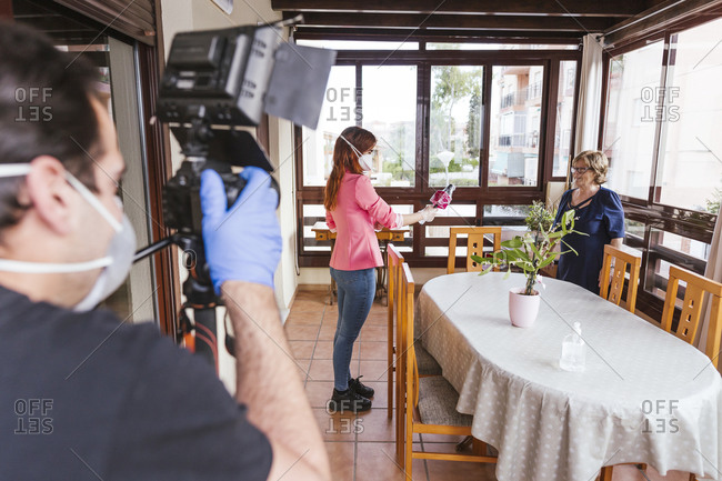 Man filming reporter interviewing senior woman at home