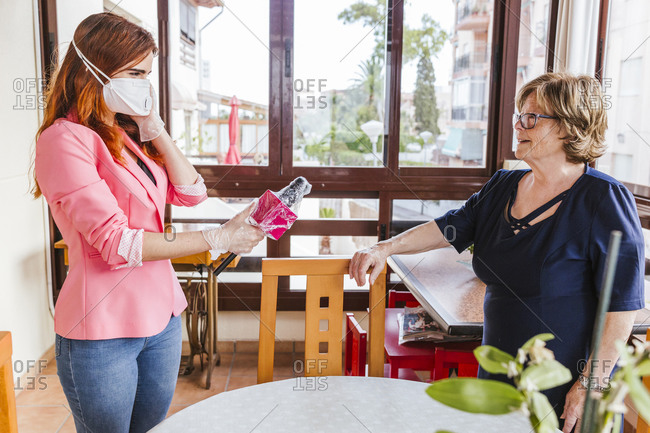 Female reporter wearing mask interviewing senior woman at home
