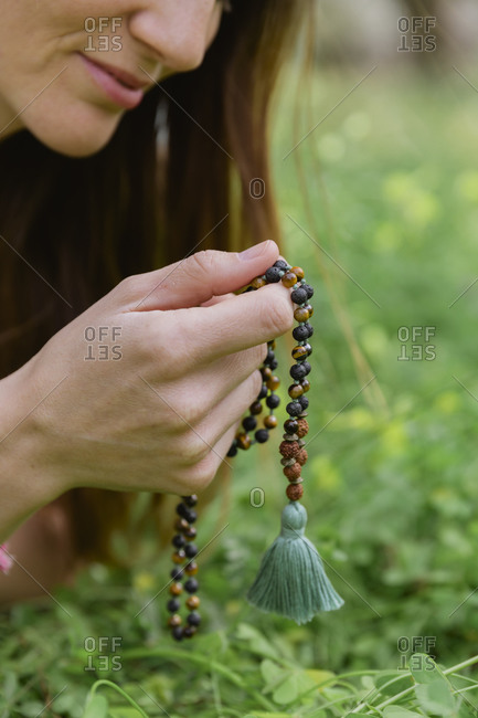 Close-up of mid adult woman holding beads meditating over grassy land
