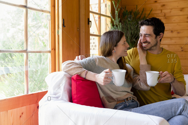 Romantic couple holding coffee mugs looking at each other while sitting on sofa in log cabin