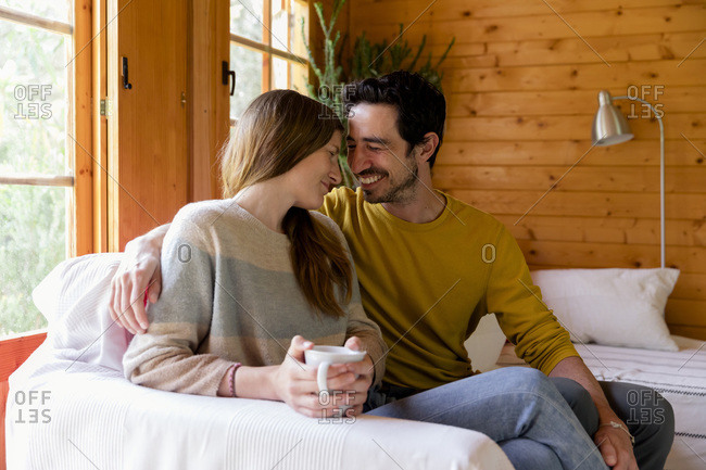 Smiling couple romancing while sitting on sofa in log cabin