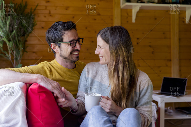 Romantic couple looking at each other while relaxing on sofa in log cabin