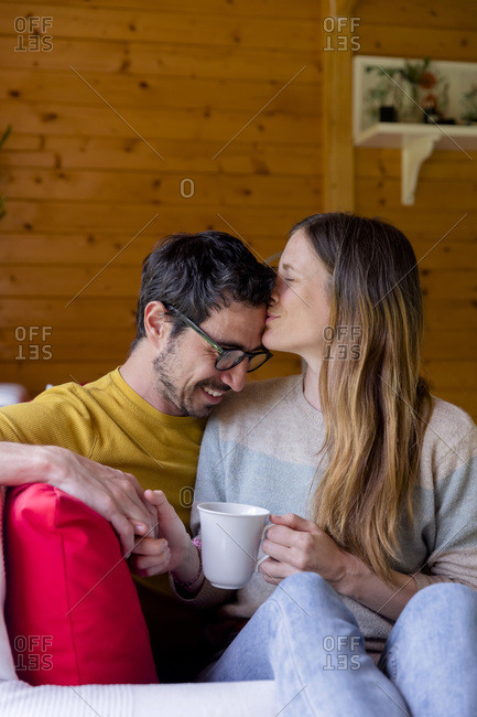 Loving woman kissing man on forehead while relaxing in log cabin