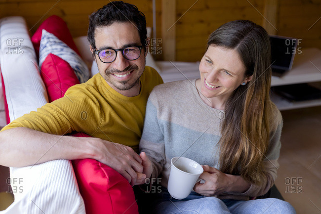 Smiling couple holding hands while relaxing on sofa in log cabin