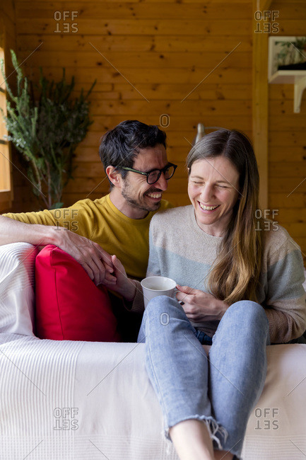Cheerful couple holding hands while relaxing on sofa in log cabin
