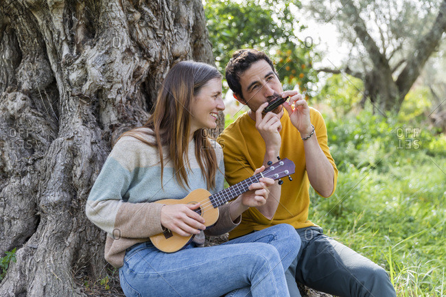 Happy couple playing musical instruments while sitting by tree trunk