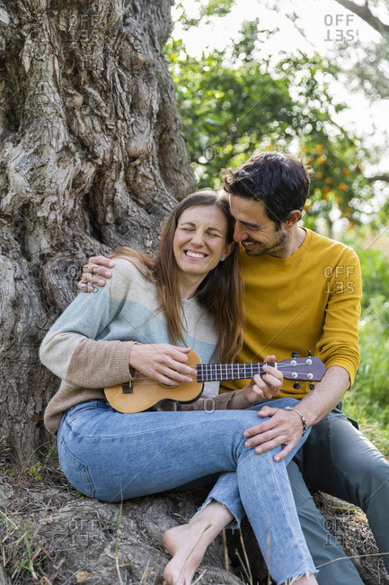 Loving man embracing happy girlfriend playing guitar while sitting against tree trunk