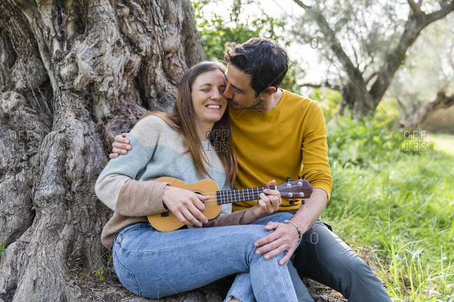 Romantic boyfriend kissing happy woman playing guitar while sitting against tree trunk