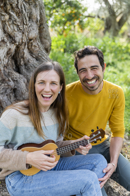 Cheerful woman playing guitar while sitting with boyfriend against tree at countryside