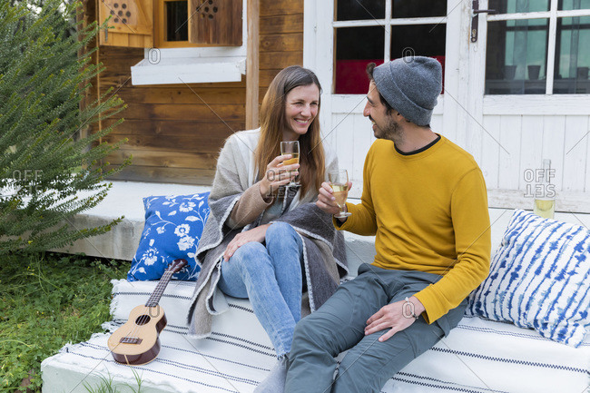 Happy couple holding wineglasses talking while sitting against log cabin