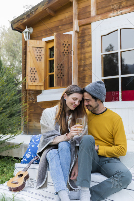 Romantic man sitting with girlfriend holding wineglass against log cabin