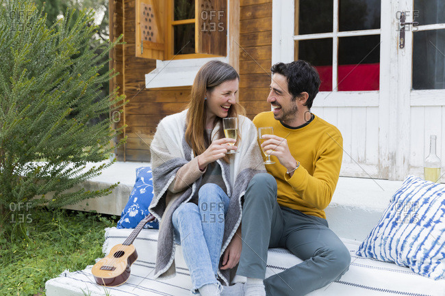 Laughing couple holding wineglasses while sitting against log cabin