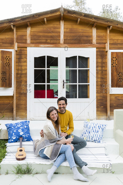 Smiling couple sitting on steps against log cabin