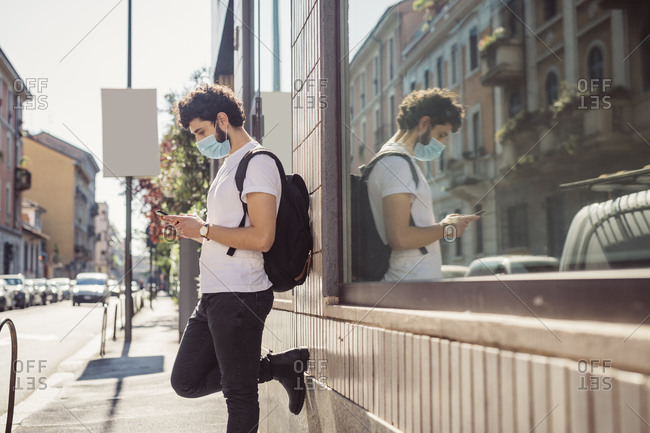 Young man wearing mask using smart phone while standing by built structure in city