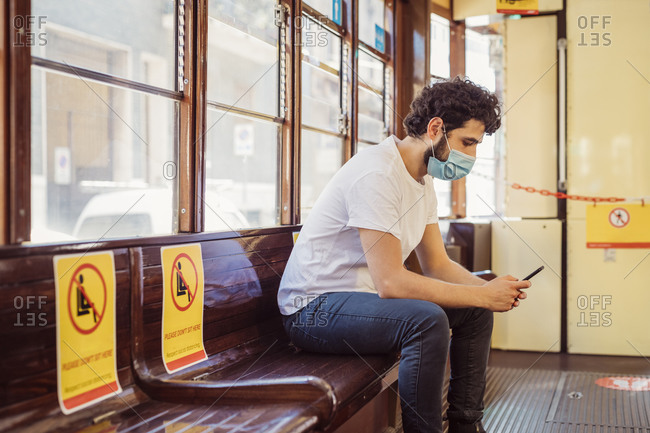 Man wearing face mask using mobile phone while sitting in tram