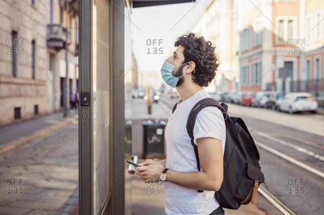 Young man wearing mask peeking through entrance of store