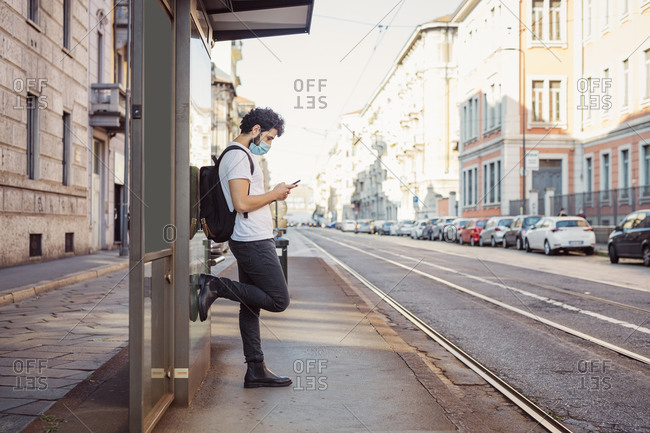 Man wearing face mask using smart phone while standing by built structure in city
