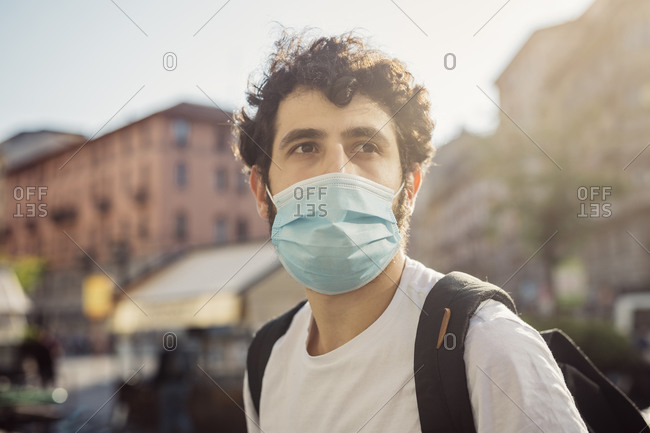 Close-up of thoughtful young man wearing face mask looking away in city