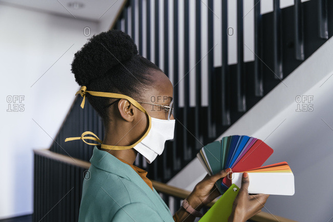 Profile of businesswoman wearing protective mask looking at color sample in staircase