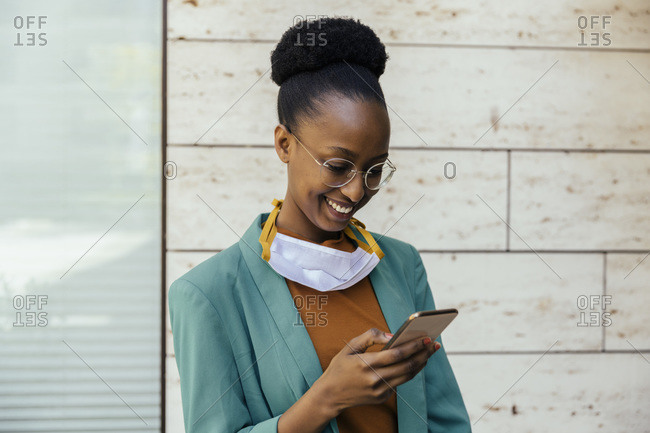 Portrait of smiling businesswoman with protective mask using smartphone