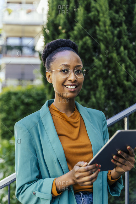 Portrait of smiling young businesswoman with digital tablet outdoors