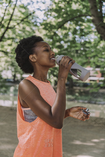 Sportive young woman drinking water from flask