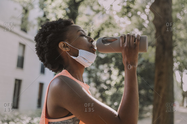 Sportive young woman with protective mask drinking water from flask