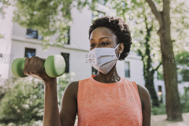 Portrait of woman wearing protective mask exercising with dumbbell outdoors