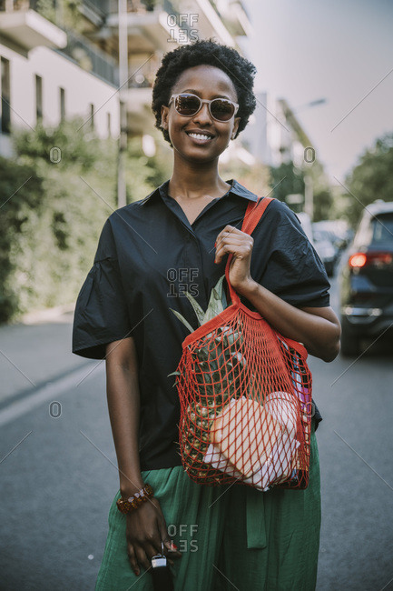 Portrait of smiling young woman standing on street with her purchase
