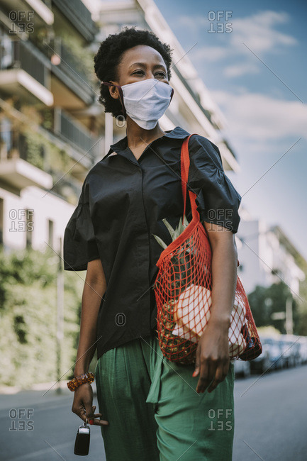 Portrait of young woman wearing protective mask standing on street with her purchase