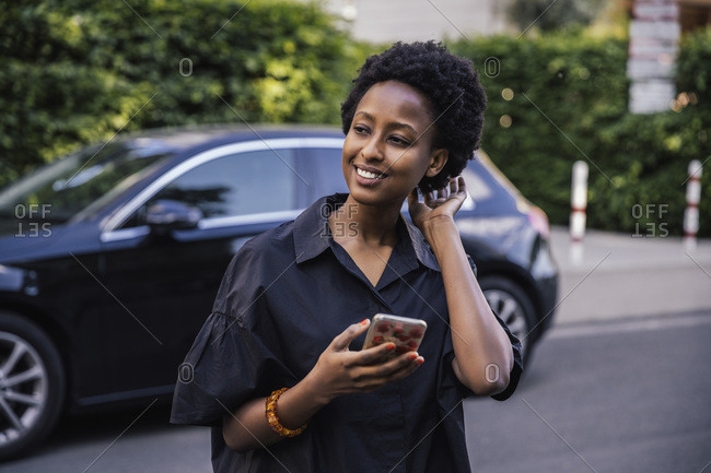 Portrait of smiling young woman with cell phone standing on the street looking at distance