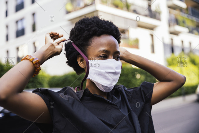 Portrait of young woman putting on protective mask outdoors