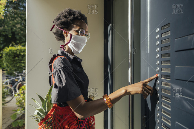 Young woman wearing textile protective mask bringing groceries to a friend