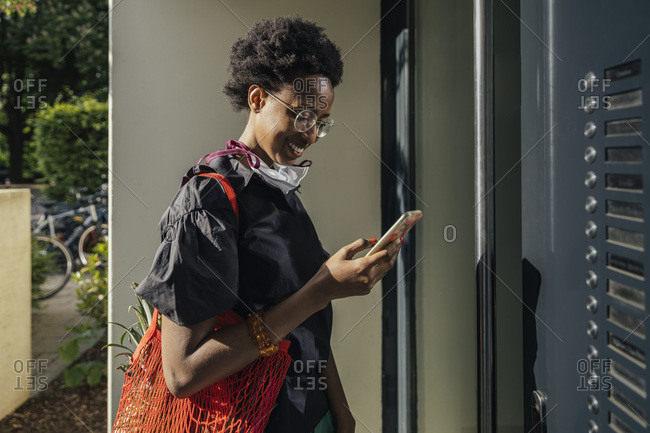 Smiling young woman with textile protective mask standing in front of entry door looking at smartphone