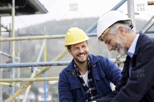 Happy architect and worker on scaffolding on a construction site