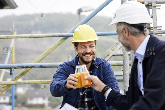 Happy architect and worker on scaffolding on a construction site clinking juice bottles