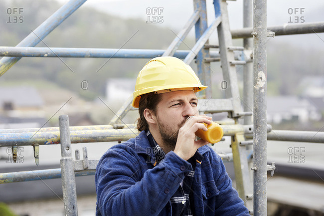 Worker drinking juice on scaffolding on a construction site