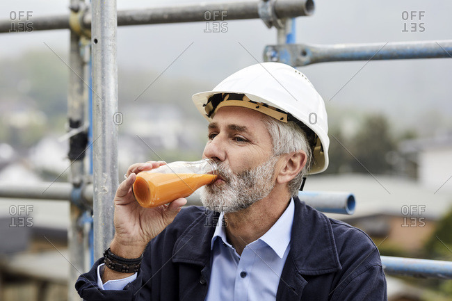 Architect drinking juice on scaffolding on a construction site