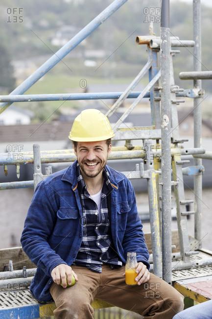 Portrait of a happy worker having a break on scaffolding on a construction site