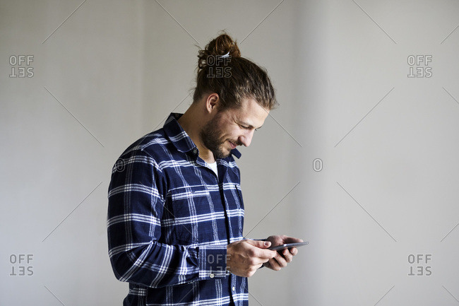 Smiling young man wearing checked shirt using smartphone