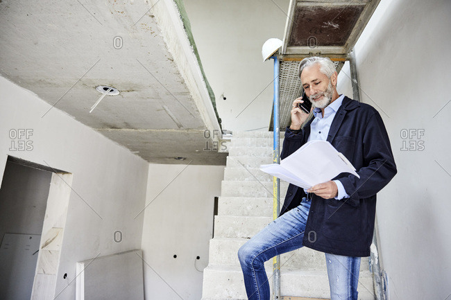 Architect on the phone holding building plan on a construction site