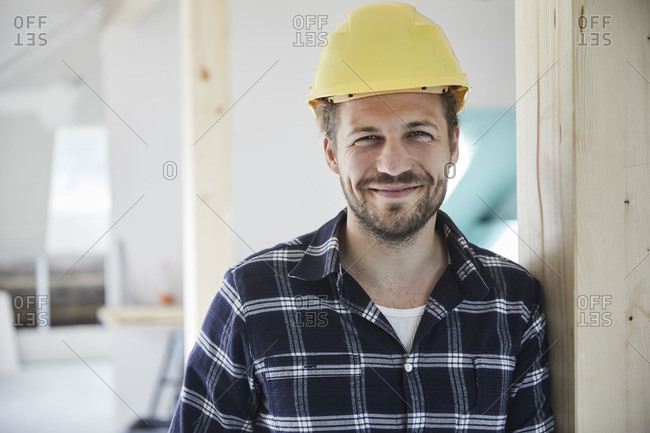 Portrait of a smiling worker wearing hard hat on a construction site