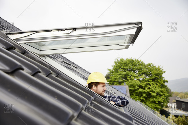 Man wearing hard hat looking out of roof window