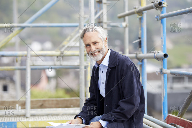 Portrait of a happy mature man on scaffolding on a construction site