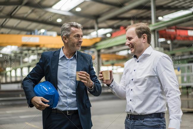 Two businessmen having a coffee break in a factory