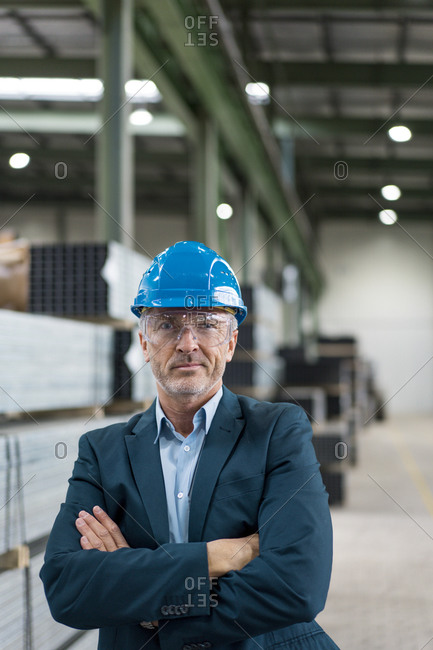 Portrait of mature businessman wearing hard hat and safety goggles in a factory