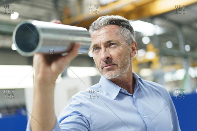 Businessman holding steel pipe in a factory