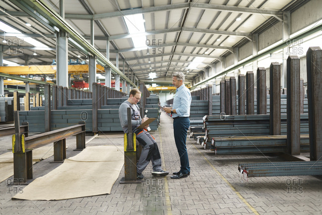 Businessman with tablet and employee with clipboard in factory storehouse