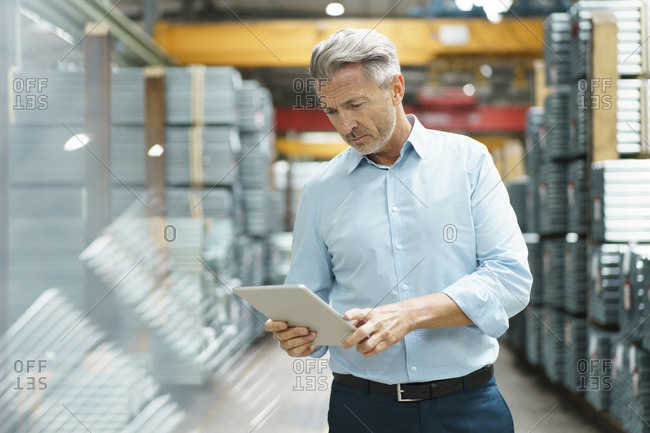 Mature businessman using tablet in a factory storehouse with steel pipes